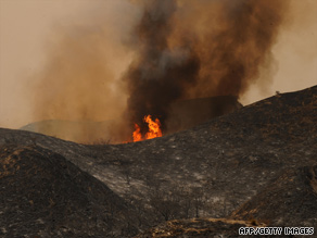 A wildfire burns close to blackened hills in the Angeles National Forest outside Los Angeles on Wednesday.