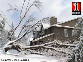 A tree pulls on utility lines Wednesday in Louisville, Kentucky, in a photo from iReporter Jacek Jasinski.