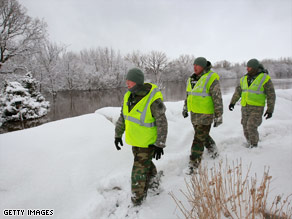 North Dakota National Guard members inspect a levee Monday along the Red River near Fargo.