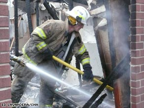 A firefighter sifts through the rubble of a burned home Friday in Midwest City, Oklahoma.