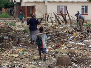 Zimbabweans walk through mounds of garbage. Lack of sanitation and clean water make cholera spread.