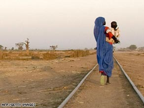 A woman left homeless by conflict in Darfur walks along railway tracks.
