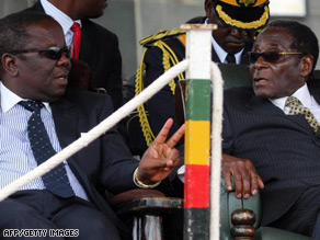 PM Morgan Tsvangirai, left, and President Robert Mugabe attend a funeral for a military commander this week.