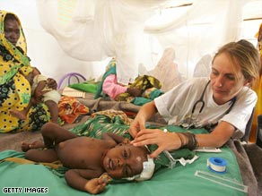 A doctor with Médecins Sans Frontières (Medics without Borders) helps a sick child in a Darfur refugee camp.