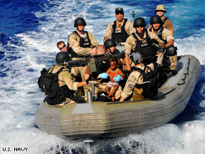 Members of the U.S. Navy take a young Somali boy to safety after rescuing him and 51 others adrift in a skiff.