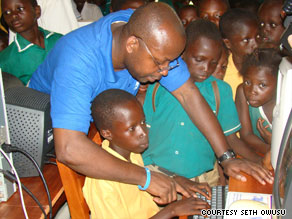 Seth Owusu shows children in his native Ghana how to use a computer during his visit in June.