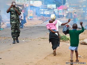 A man tries to put out a fire set in the streets of the Kasubi suburb Friday during sectarian violence.