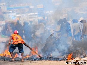 A man tries to put out a fire on Friday in Kasubi, Uganda, a suburb of Kampala.