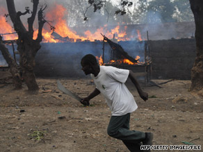 A man runs past a market set on fire in post-election violence in Nakuru, Kenya, in January 2008.