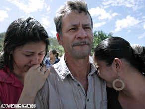 Rigoberto Vargas weeps with his daughters for his missing son on Saturday in San Miguel di Sarapiqui.