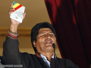 Bolivian President Evo Morales celebrates the first results by holding the new Constitution in La Paz Sunday.