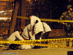 Police inspect one of two dead bodies after an explosion Tuesday night in Bogota, Colombia.