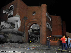 Residents check out a destroyed police building after a car bombing Sunday night in Cali, Colombia.