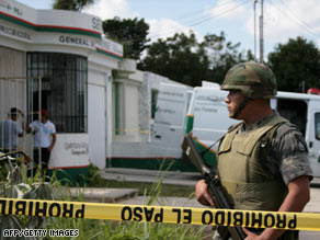 A soldier guards the forensics office where the body of a slain former general was taken in Cancun, Mexico.