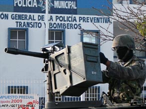 A Mexican soldier guards the entrance at a Canc�n police station where the military is investigating a murder.