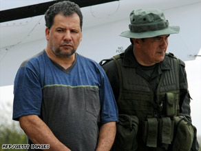Police escort suspected drug kingpin Daniel Rendon Herrera, left, on Wednesday in Bogota, Colombia.