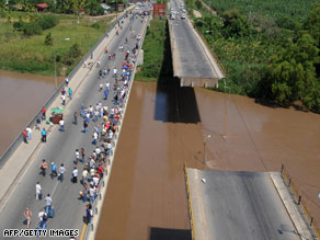 Thursday's quake leaves part of a bridge damaged over the Ulua River in El Progreso, Honduras.