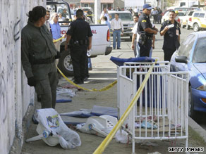 A crib and baby seats sit outside the scene of a deadly day care center fire in Mexico.