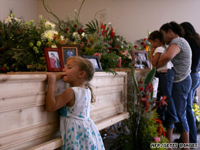 A girl stands at the coffin of Mormon church leader Benjamin LeBaron in Chihuahua State.