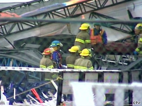 Rescue workers remove a victim from the debris caused by Saturday's stage collapse at the Big Valley Jamboree.