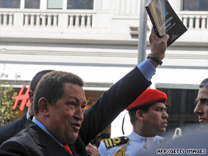 Venezuelan President Hugo Chavez waves a book Friday during a visit to Madrid, Spain.