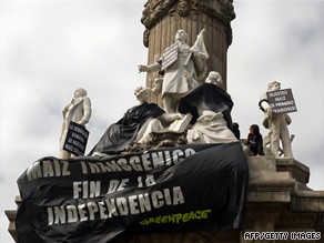 A Greenpeace banner protesting genetically modified corn hangs on a Mexico City monument on Sunday.