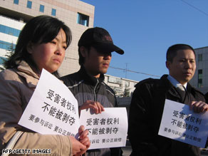 Victims' relatives outside a court hold banners that read &quot;cannot deprive the victims' rights.&quot;