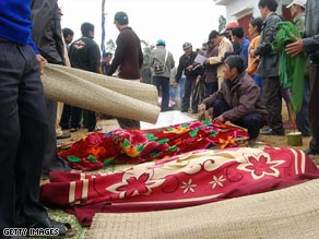 People stand around bodies of victims from the river boat accident.