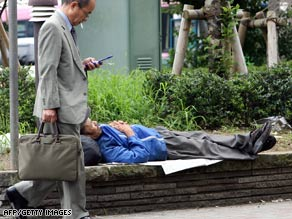 A businessman walks past a homeless man taking a nap at a Tokyo park.