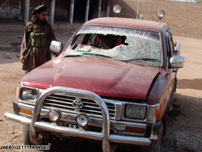 A man stands beside a damaged vehicle after a Pakistani attack on Taliban militants on the Afghan border.