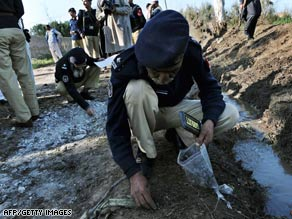 Policemen collect evidence after an explosion on security forces outside Peshawar, Pakistan, Saturday.