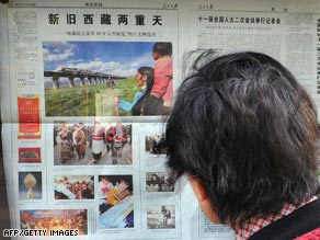 A woman reads a state media newspaper Saturday in Beijing with coverage of Tibet.