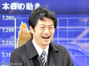 A businessman is all smiles on Wednesday as he passes by a share prices board in Tokyo.