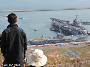 South Koreans look at the USS John C. Stennis and the USS Blue Ridge in Busan Wednesday.