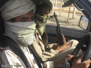 Taliban militants pose with their weapons as they drive their car in Wardak province. (File photo)