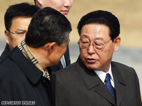Kim Yong-Il, right, chats with his aides as he arrives at the Beijing Capital International airport on Tuesday.