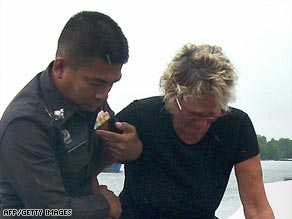 Linda Robertson is helped by Thai police after her husband was allegedly murdered by pirates.