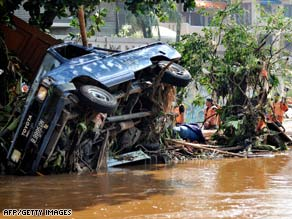 Members of a search and rescue team look for bodies around upended trees and vehicles near  Jakarta Friday.