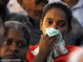 A relative of a deceased serviceman wipes away tears Monday at ceremonies at a Colombo suburb.