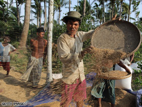 Farmers sift grain during the rice harvest on April 27 in the Irrawady delta village of Ma Lot Myit Than.
