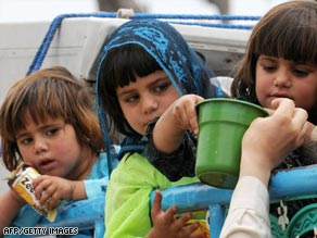 Displaced children from Buner receive food as they travel on a packed vehicle.