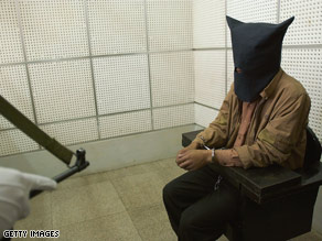 A Chinese policeman guards an illegal trafficker at a detention cell in Kunming, Yunnan Province, China.