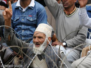 A Kashmiri man, sitting behind a barbed wire fence, gestures during an election rally in Srinagar.
