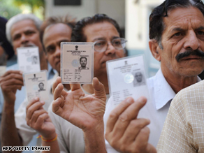 Indians voters hold up their voter ID cards at a polling station in northern India.
