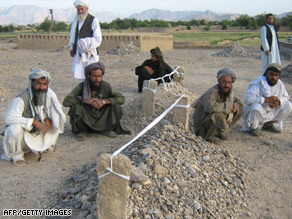 Villagers sit near the graves of victims of airstrikes in Garni, in western Farah province.