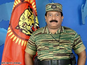 In this picture taken 27 November 2003, Velupillai Prabhakaran stands next to an LTTE flag.