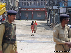 Indian paramilitary forces stand guard as a curfew goes into effect in Srinagar on Monday.
