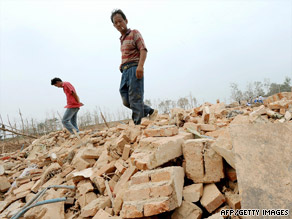 Villagers walk on the rubble of workshops after an explosion in east China's Anhui province on Sunday.