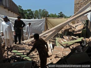 Residents sift through the rubble of a bombed out school near Peshawar city.