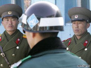 N. Korean army soldiers, back, look at a S. Korean soldier, center, in the demilitarized zone in June.